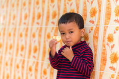 Kid eating cracker. With flower-picture wall royalty free stock photos