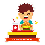 Kid eating and drinking at fast food table Royalty Free Stock Photo