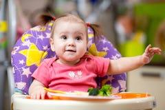 Kid eating food on kitchen Royalty Free Stock Photos