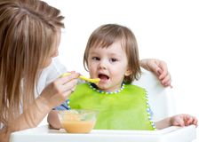 Kid eating food on kitchen Royalty Free Stock Photos