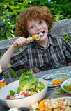 Kid eating fruit. Young boy (7) enjoying a healthy skewer with fruit at an outdoor barbecue Stock Photography