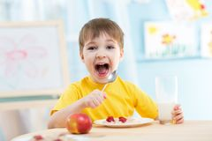 Kid eating healthy food at home Stock Images
