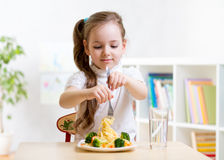 Kid eating healthy food at home. Child girl eating healthy food at home or kindergarten royalty free stock photo