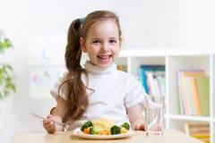 Kid eating healthy food at home Stock Photos