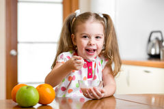 Kid eating healthy food in kitchen Stock Photo