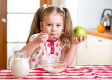 Kid eating healthy food in kitchen Royalty Free Stock Image