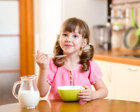 Kid eating healthy food in kitchen Stock Image