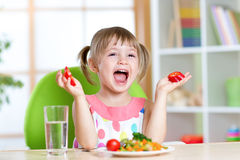 Kid eating healthy vegetables food at home or Royalty Free Stock Photography