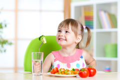 Kid eating healthy vegetables meal in home Stock Photos