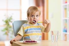 Kid eating healthy vegetables at nursery room Stock Image