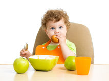 Kid eating by himself Stock Photos
