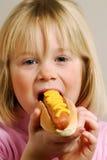 Kid eating hot dog. Stock Image