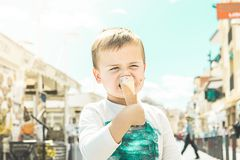 Child eating ice cream on the street stock images