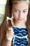 Kid Eating Ice Cream. Young girl / child staring at a chocolate ice cream on a stick melting in her hands Royalty Free Stock Photography
