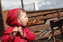 Kid eating a kebab Stock Images