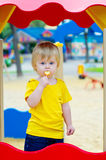 Kid eating lollipop on the playground Royalty Free Stock Image