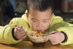 Kid eating noodles Royalty Free Stock Photo