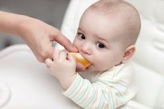 Kid eating orange Royalty Free Stock Images
