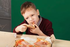 Kid eating pizza slice from the box at fast food restaurant. Children eat Italian pizza in the cafe. School boy is eating pizza for lunch. Child unhealthy meal royalty free stock photo