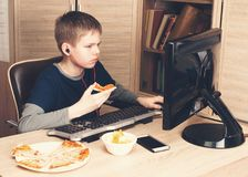 Kid eating pizza and surfing on internet or watshing video on PS Royalty Free Stock Images