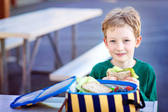 Kid eating school lunch. Beautiful positive schoolboy enjoying healthy lunch during recess outdoor Stock Image