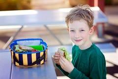 Kid eating school lunch Stock Image