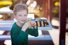 Kid eating school lunch. Beautiful positive schoolboy enjoying healthy lunch during recess outdoor Royalty Free Stock Image