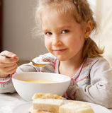 Kid eating soup Stock Images