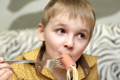 Kid eating spaghetti with sausage Stock Photography
