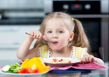 Kid eating spaghetti with vegetables in nursery Stock Images
