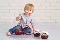 Kid eating strawberry jam Royalty Free Stock Image