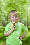 Kid eating a tasty ice cream outdoors Royalty Free Stock Photos