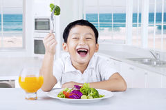 Kid eating vegetables salad in the kitchen Stock Photography
