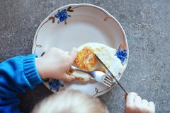 Kid eats fried egg with fork stock images