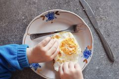 Kid eats fried egg with hands, knife and fork Royalty Free Stock Photography