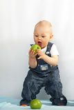 Kid eats green apple Royalty Free Stock Photos