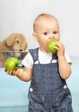 Kid eats green apple Royalty Free Stock Images