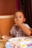 Kid eats. Little boy learning to eat with a fork and spoon royalty free stock images