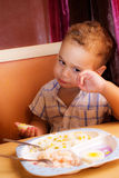 Kid eats. Little boy learning to eat with a fork and spoon royalty free stock photography