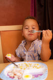 Kid eats. Little boy learning to eat with a fork and spoon stock images