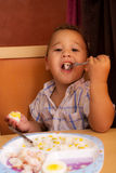 Kid eats. Little boy learning to eat with a fork and spoon stock image