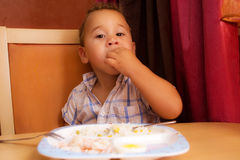 Kid eats. Little boy learning to eat with a fork and spoon stock photography
