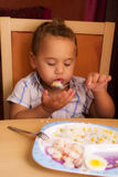 Kid eats. Little boy learning to eat with a fork and spoon royalty free stock photo