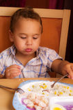 Kid eats. Little boy learning to eat with a fork and spoon stock photo