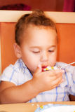 Kid eats. Little boy learning to eat with a fork and spoon royalty free stock image