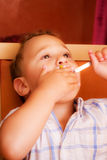 Kid eats. Little boy learning to eat with a fork and spoon stock photos