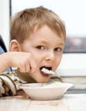 Kid eats porridge Stock Photo