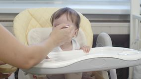 Kid eats porridge from spoon sitting on highchair in kitchen. Baby learns to eat porridge from spoon sitting on highchair in the kitchen stock video footage