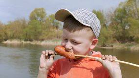The kid eats the sausage with his teeth, strung on the willow twig with pleasure. Ultra HD, 4K stock video