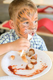 Kid eats a sausage Royalty Free Stock Images